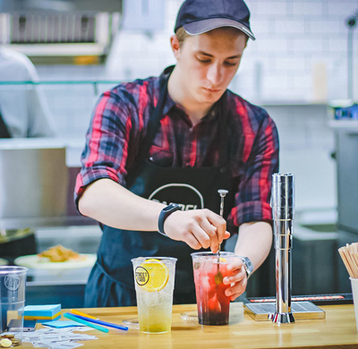 This is a photo of a man working in a kitchen making a refreshing summer drink.