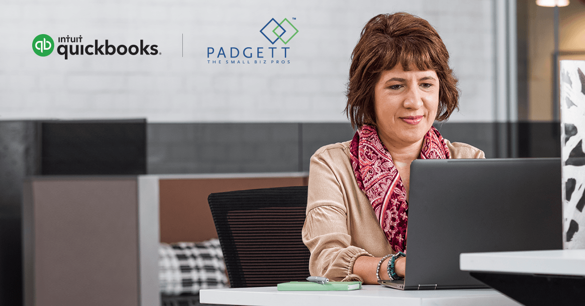 This is a photo of a woman at a laptop. The QuickBooks logo and the Padgett logo are on the wall behind her.